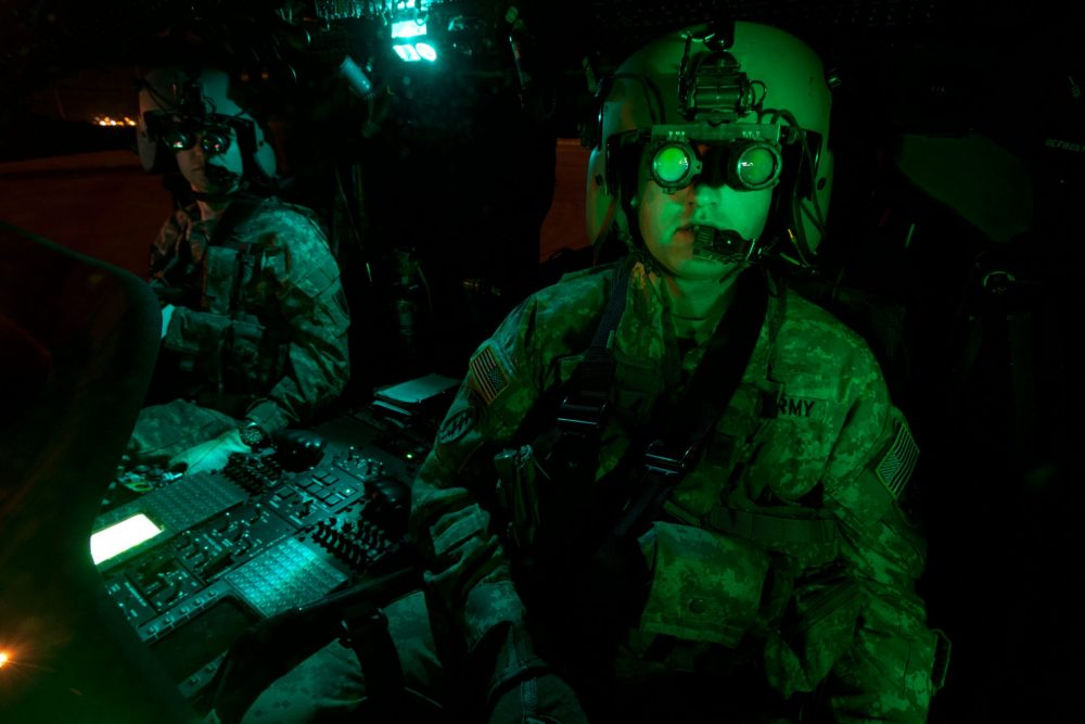 D84RM3 Pilots equipped with night vision goggles in the cockpit of a UH-60 Black Hawk